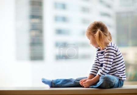 Little girl looking at window