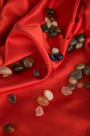 Color precious stone on red silk