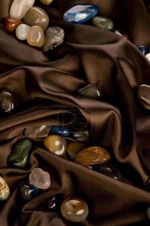 Color precious stone on brown silk