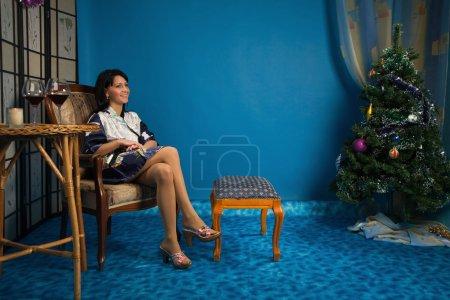 Photo pour Belle femme assise dans un fauteuil dans le salon - image libre de droit