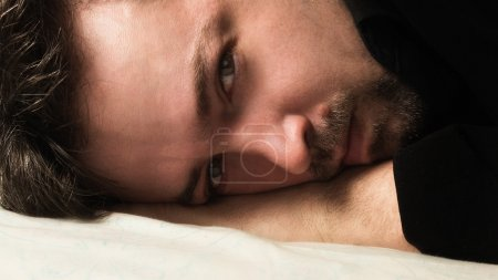 Attractive man lying on a bad