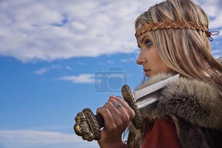 Photo for Blonde girl in the Scandinavian suit on a blue sky background - Royalty Free Image