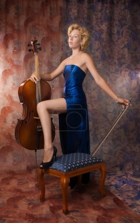 Photo for Attractive woman in evening dress posing with cello - Royalty Free Image