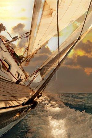 Photo pour Voilier récolte pendant les régates au coucher du soleil océan - image libre de droit