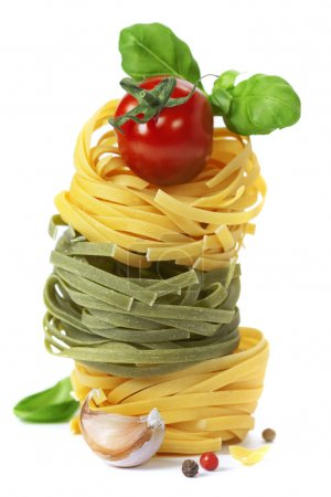 Photo for Italian pasta fettuccine nests with tomato and basil isolated on white background - Royalty Free Image