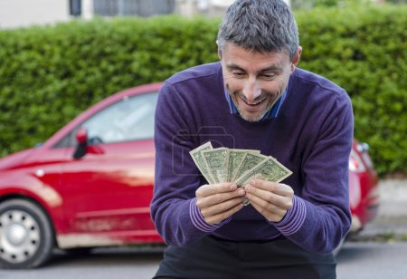 Photo for Making Money Selling Cars, Man shows Dollars - Royalty Free Image