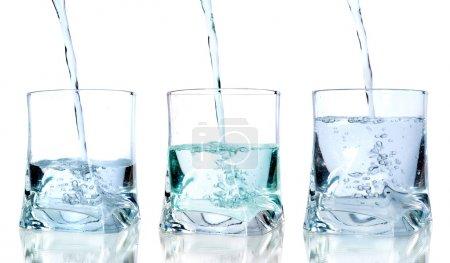 Photo pour Eau fraîche versant dans un verre sur fond blanc en séquence - image libre de droit