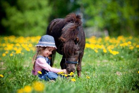 Photo pour Enfant et le petit cheval dans le champ au printemps. - image libre de droit