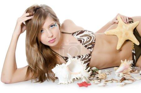 The young girl in bikini lays with seashells