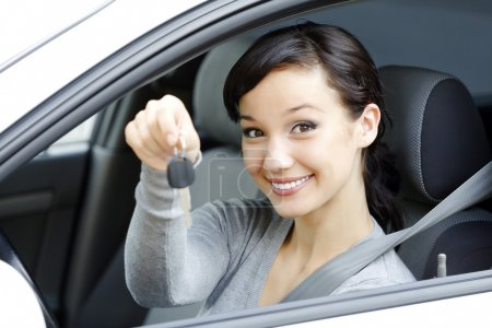 Photo for Pretty female driver in a white car showing the car key. - Royalty Free Image