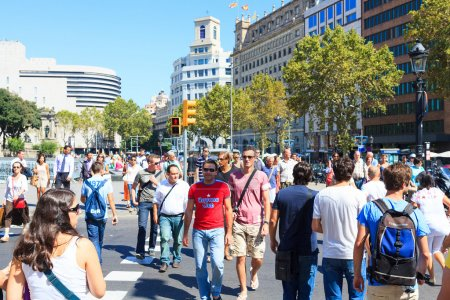 Many of tourists strolling across the center of Barcelona, Spain