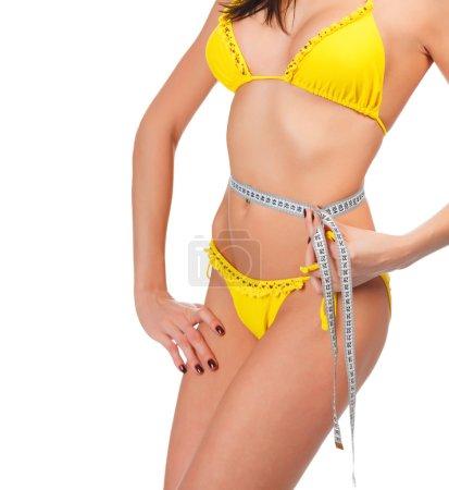 Beautiful woman measuring her waist