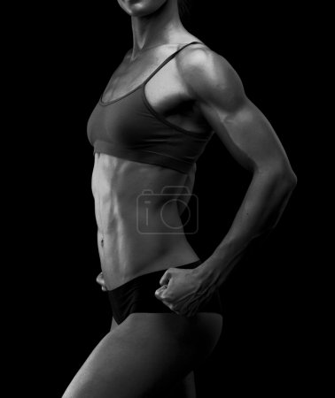 Black and white image of a muscular female body against black ba
