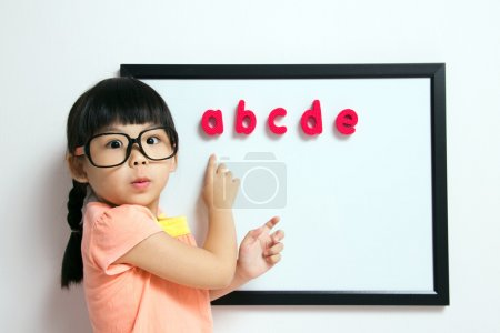 Photo for School girl wears a big spectacles posing next to a white board - Royalty Free Image