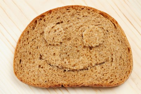 Photo for Bread slice as smiling face on wooden board - Royalty Free Image
