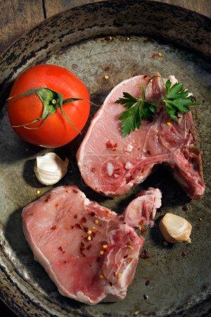 Photo pour Côtelettes de porc cru frais avec tomate et ail - image libre de droit