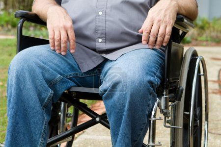 Photo for Torso and leg view of paraplegic man as he sits outside in his wheelchair. - Royalty Free Image