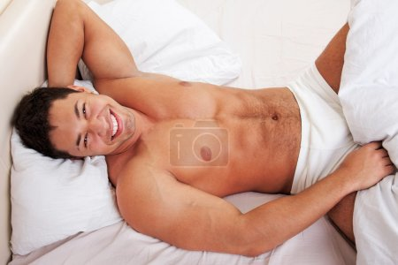 Photo for Attractive man lying in his bed smiling - Royalty Free Image
