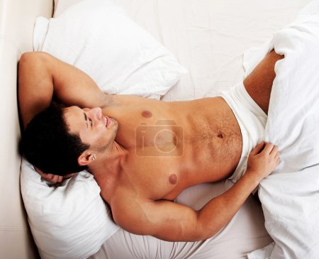 Attractive man lying in his bed smiling