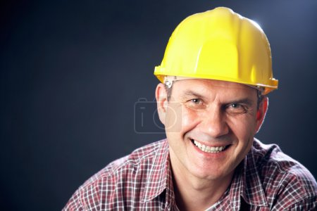 Photo for Horizontal portrait of a smiling handsome man-builder on a dark background - Royalty Free Image