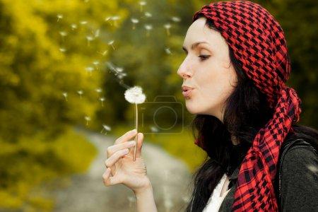 Girl blowing on dandelion