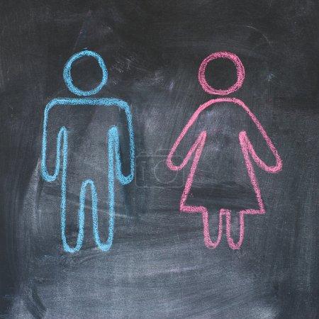 Photo pour Figures d'homme et de femme sur un tableau noir, dessin à la craie - image libre de droit