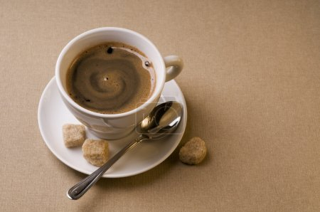 Photo for Black coffee cup with brown sugar over textured background - Royalty Free Image