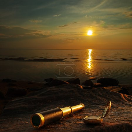 Photo for Antique brass telescope and compass at sea coast stone - Royalty Free Image
