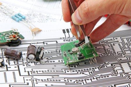 Photo pour Une main avec une pince à épiler tenant une carte de circuit électronique sur le fond du schéma électronique - image libre de droit