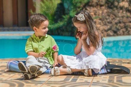 Foto de El niño le da a la niña una flor. - Imagen libre de derechos