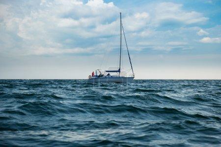 Photo pour Un yacht dans une mer orageuse. un bateau abaissé les voiles et méconnaissable - image libre de droit