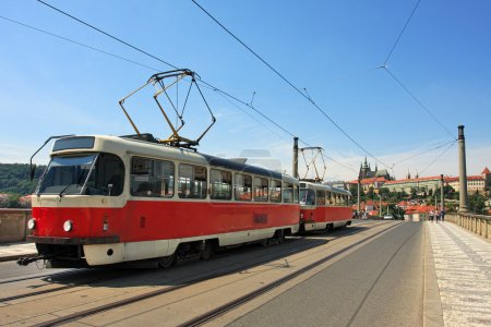 Photo pour Tram rouge passant sur le pont de Manes (Manesuv Most) et célèbre château de Prague à l'arrière-plan à Prague, République tchèque . - image libre de droit