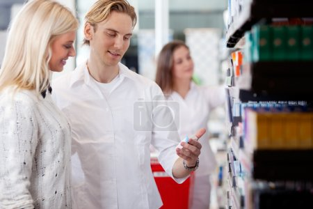 Pharmacist And Customers At Pharmacy