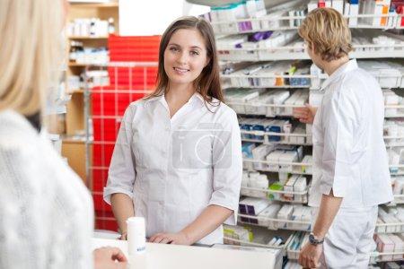 Pharmacist Attending Customer at Counter