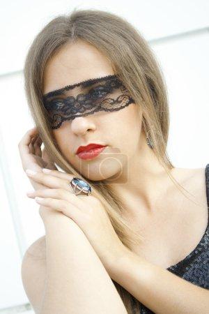 Photo pour Mystérieuse jeune fille assez à la mode les yeux bandés ruban de dentelle noire sur un anneau de doigt avec une grande pierre bleu - image libre de droit