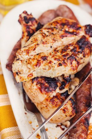 Marinated grilled chicken steaks and sausages on a plate