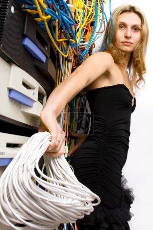 Photo pour Technicien femmes se penchant sur la baie de serveur tenant la bobine de fil - image libre de droit