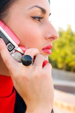 Gorgeous emotional brunette wearing red dress with mobile phone