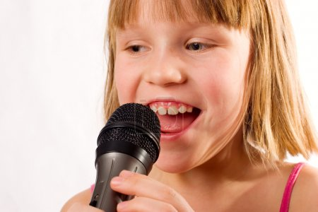 Pretty litle girl singing in microphone isolated over white
