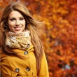 Young woman with autumn leaves in hand and fall ye...