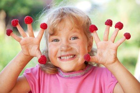 Photo pour Joyeux petit enfant avec framboise en plein air - image libre de droit