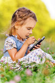 Little girl writes stylus on device