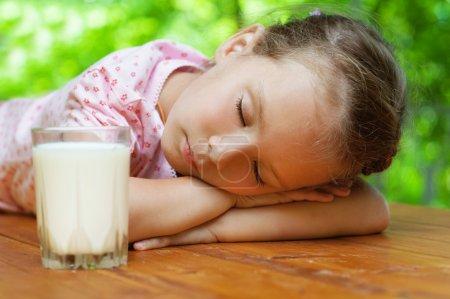 petite fille dort autour d'un verre de lait
