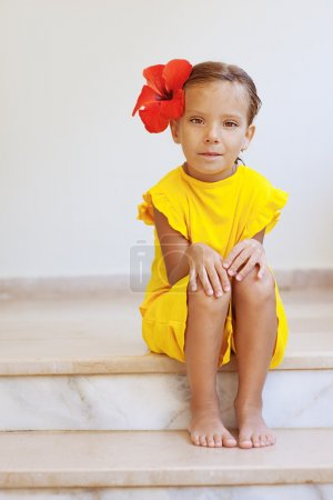 Little girl in yellow dress with red flower