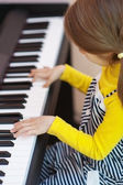 Little girl in yellow dress plays piano