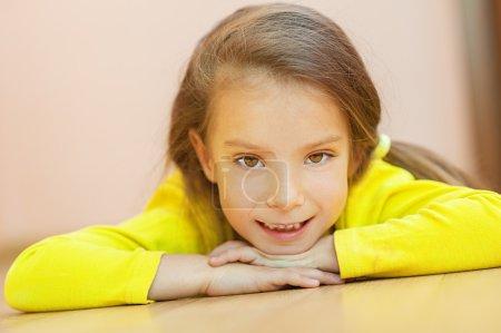 Photo pour Belle petite fille en robe jaune couchée sur le sol et riant . - image libre de droit