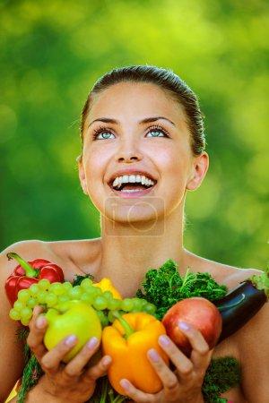 Foto de Retrato de mujer joven hermosa con hombros desnudos con frutas y hortalizas - manzanas, berenjena, pimiento, perejil, uvas, sobre la naturaleza de fondo verde verano. - Imagen libre de derechos