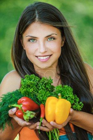 Foto de Retrato de mujer joven hermosa con hombros desnudos sosteniendo un vegetal - perejil, pimienta, berenjena, sobre la naturaleza de fondo verde verano. - Imagen libre de derechos