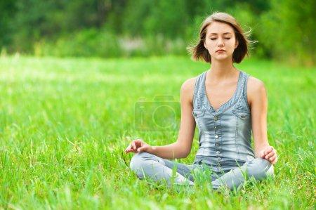 Photo pour Jeune, jolie femme assise sur l'herbe verte (prairie, clairière) jambes croisées en position lotus méditant - image libre de droit