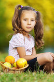 Child is sitting on the grass with fruit